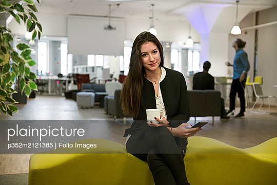 Young woman holding smart phone on office sofa - p352m2121385 by Folio Images