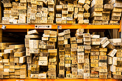 Large selection of wooden planks stacked on shelves in a warehouse. - p1100m1575737 by Mint Images