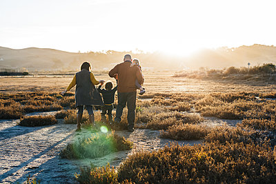 Back view of Family holding hands against sun flare at natural park. - p1166m2095075 by Cavan Images