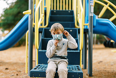 A boy looking sad at a playground with his face mask on - p1166m2218385 by Cavan Images