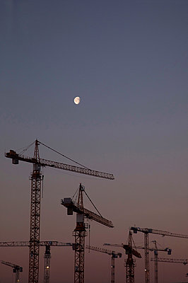 Construction cranes and moonlight - p382m2178438 by Anna Matzen