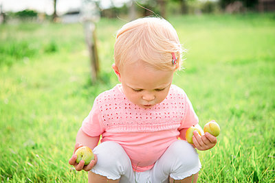 Cute female toddler squatting on grass looking down - p429m2098227 by Senserini Lucrezia