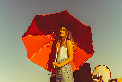 Junge Frau steht gut gelaunt auf Hausdach - p432m2219693 von mia takahara
