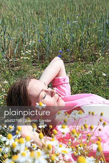 Sunbathing young woman - p0452769 by Jasmin Sander