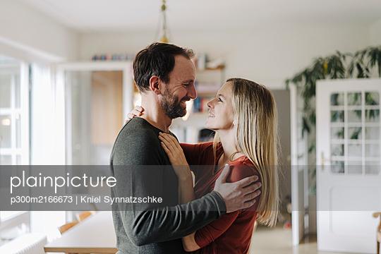 Happy couple embracing in their comfortable home - p300m2166673 von Kniel Synnatzschke