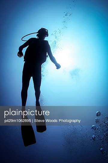 Silhouetted male scuba diver in ocean, Bali, Indonesia - p429m1062895 by Steve Woods Photography