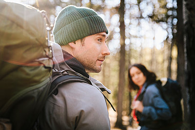 Couple with backpacks hiking in sunny woods - p1192m2093986 by Hero Images