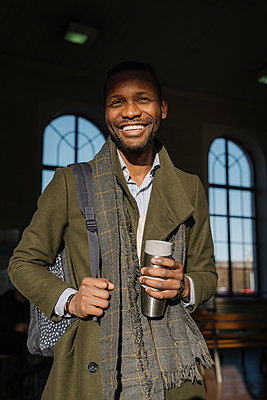 Portrait of happy stylish man with reusable cup in the train station - p300m2155260 by Hernandez and Sorokina