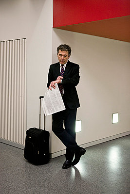 A businessman waiting with his suitcase and holding a newspaper - p3018585f by Halfdark