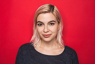 Portrait of woman with bleached hair and smiling against red background - p301m2039713 by Vladimir Godnik