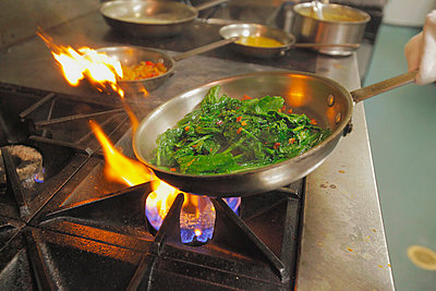 Frying pan full of greens in a restaurant kitchen; boston massachusetts usa - p442m839607 by Eric Kulin