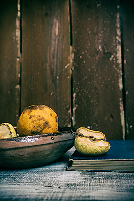 Rotten fruits with old book on the table  - p794m2031125 by Mohamad Itani