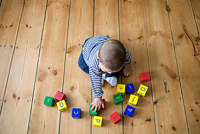 Baby boy playing with building blocks - p9244732f by Image Source