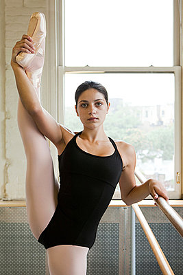 Ballerina stretching leg - p9245517f by Image Source