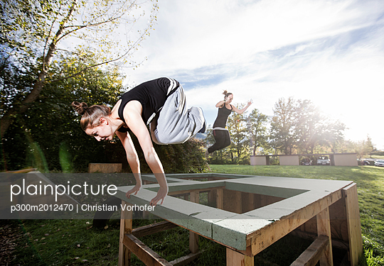 Woman jumping over barrier during freerunning exercise - p300m2012470 von Christian Vorhofer