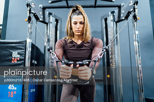 Woman exercising at cable machine in gym - p300m2167408 by Oscar Carrascosa Martinez