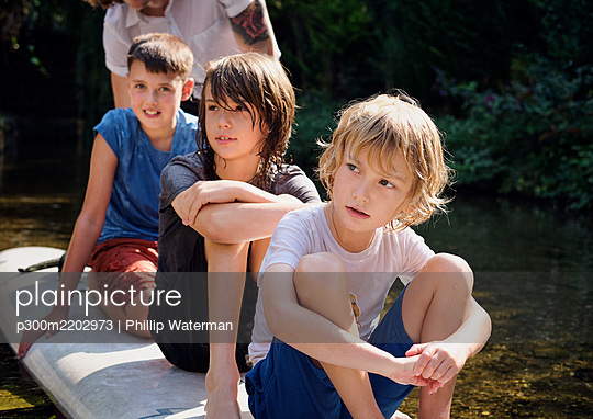 Thoughtful boys sitting on paddleboard in stream at forest - p300m2202973 by Phillip Waterman