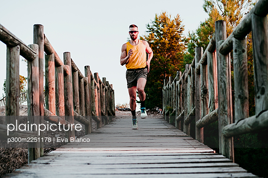 Muscular male athlete running on boardwalk against clear sky during sunset - p300m2251178 by Eva Blanco