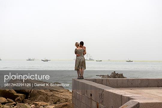 Lesbian couple embraces on the promenade - p817m2291126 by Daniel K Schweitzer