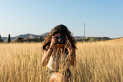 Young woman is taking a picture with a camera in a meadow at sun - p1166m2129531 by Cavan Images