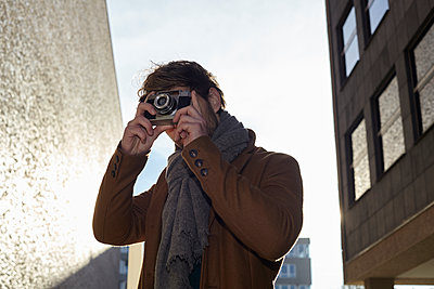 Young man taking a picture with vintage camera - p300m1188684 by Jo Kirchherr