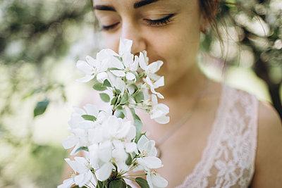 Middle Eastern woman smelling flowers - p555m1481908 by Aleksandr Kuzmin