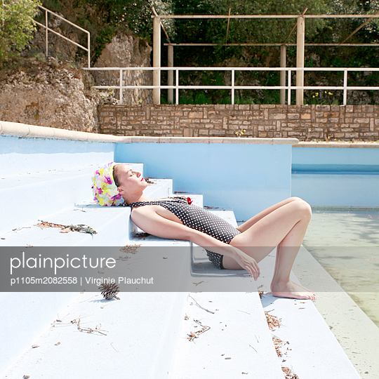 Woman on steps by open air swimming pool - p1105m2082558 by Virginie Plauchut