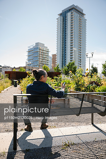 Man with smart phone on bench in sunny, urban community garden - p1192m2130076 by Hero Images