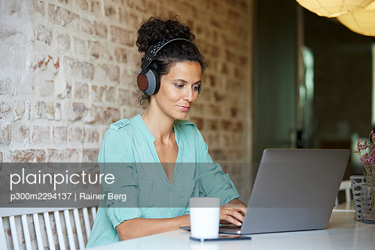 Businesswoman with wireless headphones using laptop at desk in office - p300m2294137 by Rainer Berg