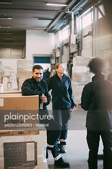 Male entrepreneur sitting on box container by colleagues at distribution warehouse - p426m2239363 by Maskot