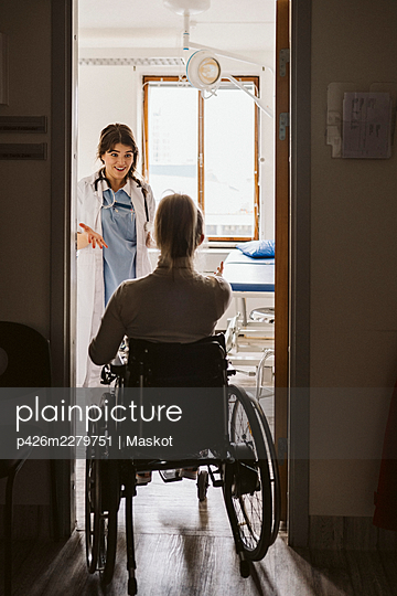 Disabled woman visiting female doctor at medical clinic - p426m2279751 by Maskot