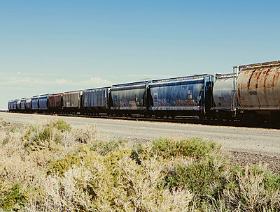 Row of container freight wagons of a freight train crossing the plains near Wendover. Scrubby sage bushes growing by the track.  - p1100m876038f by Paul Edmondson