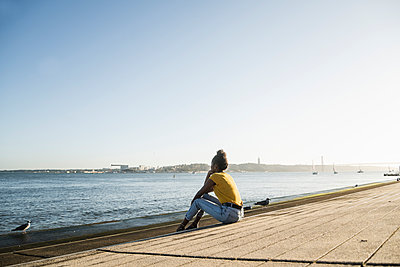 Rear view of young woman sitting at the waterfront at sunset, Lisbon, Portugal - p300m2160389 by Uwe Umstätter