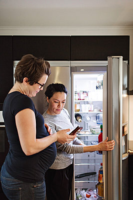 Woman showing mobile phone to girlfriend while standing by open refrigerator in kitchen - p426m1579971 by Maskot