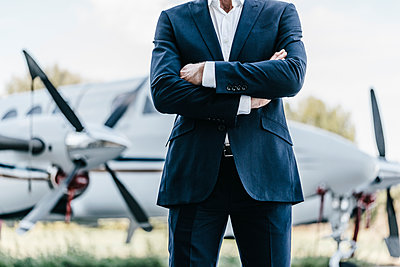 Businessman in front of propeller plane - p586m1208622 by Kniel Synnatzschke