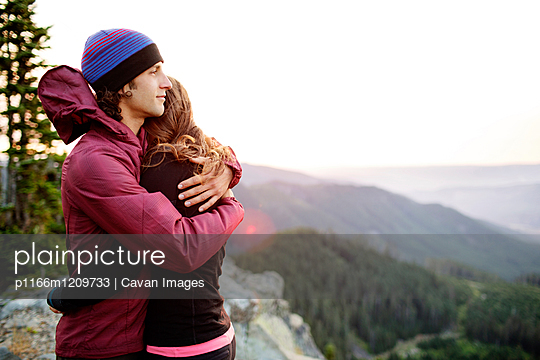 Couple embracing while standing on top of mountain against clear sky - p1166m1209733 by Cavan Images
