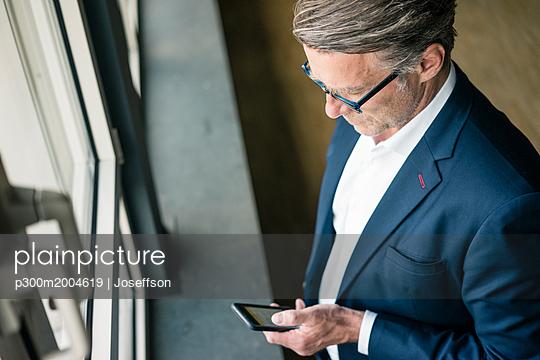 Mature businessman standing at the window using cell phone - p300m2004619 von Joseffson