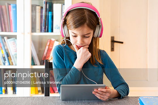 Little girl doing homework with headphones and digital tablet - p300m2104056 von Larissa Veronesi