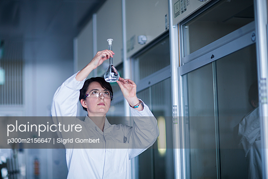 Female chemist at work examining a liquid - p300m2156647 by Sigrid Gombert