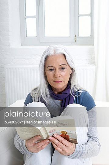 Aeltere Frau liest ein Buch  - p6430237f von senior images RF