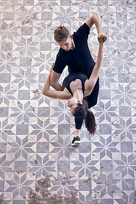 High angle view of ballet dancers dancing together on floor in old building - p1166m2024687 by Cavan Images