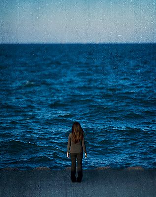 Woman looking out over water - p1614m2185783 by James Godman