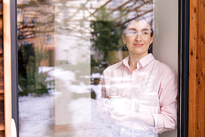 Smiling female entrepreneur with coffee mug looking away seen through glass window - p300m2266627 by Katharina Mikhrin