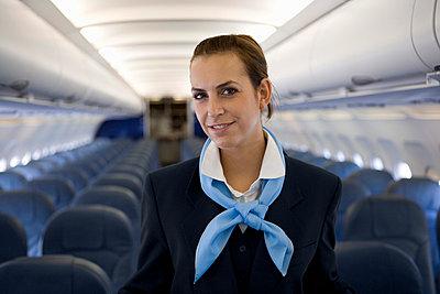 A flight attendant standing in the cabin of a plane - p3018288f by Halfdark