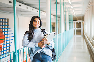 Portrait of young female student in corridor of university - p426m2194934 by Maskot