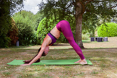 Woman practicing yoga in garden, downward facing dog - p429m2032207 by Image Source