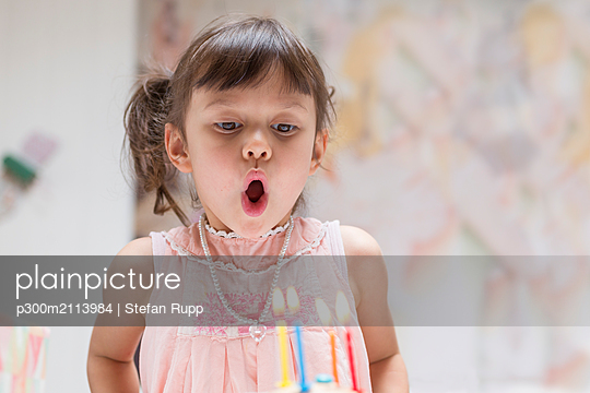 Portrait of little girl blowing out burning candles on her birthday cake - p300m2113984 von Stefan Rupp