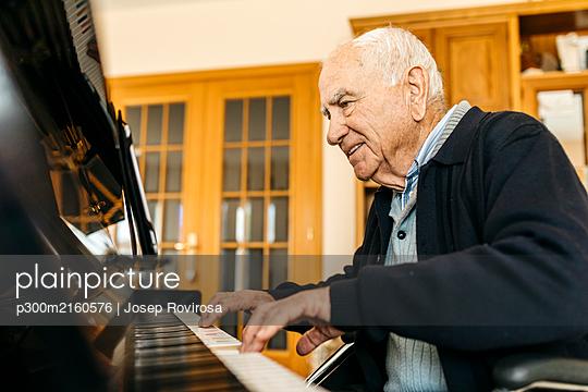 Smiling senior man sitting in wheelchair playing piano at home - p300m2160576 by Josep Rovirosa