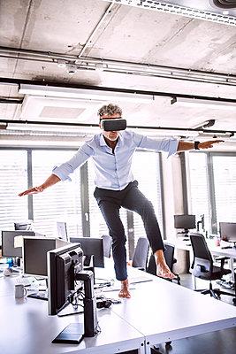 Barefoot mature businessman on desk in office wearing VR glasses - p300m1568089 von HalfPoint