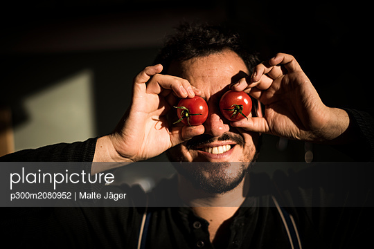 Man covering his eyes with tomatoes - p300m2080952 by Malte Jäger